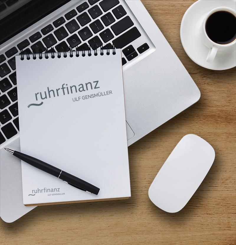 notizblock von ruhrfinanz liegt mit kugelschreiber auf einem laptop